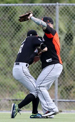 外野の守備練習中にバーンズ(右)と接触するマーリンズのイチロー(共同)