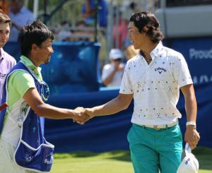 通算7アンダーで終えて佐藤キャディー(左)と握手を交わす石川(撮影・亀山泰宏)